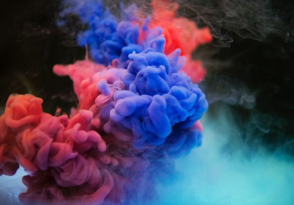 Abstract photograph of red and blue smoke on a black background